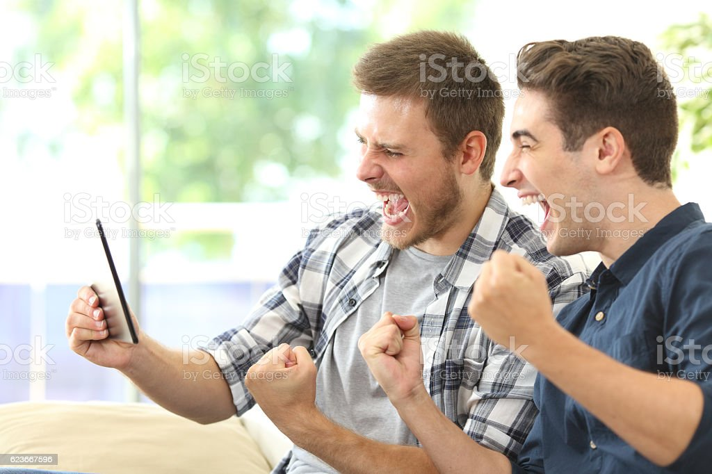 Excited friends watching tv on a tablet stock photo