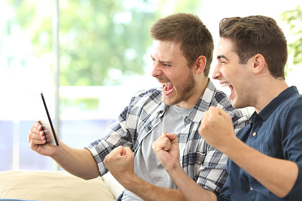 excited friends watching tv on a tablet - jeu photos et images de collection
