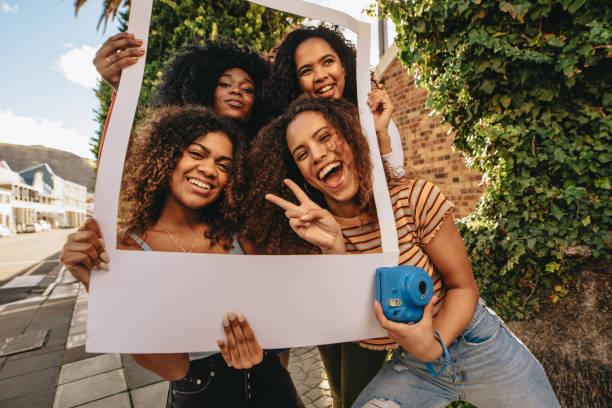 Aufgeregte Freunde mit leerem Fotorahmen – Foto