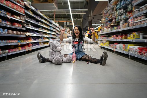 926078666 istock photo Excited funny woman sitting at the floor in supermarket and holding lollipops 1220334768