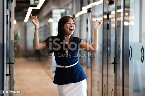 465474428istockphoto Excited funny young asian businesswoman celebrate success in victory dance 1180590215