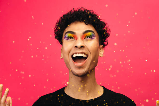 Excited gay man throwing glitter stock photo