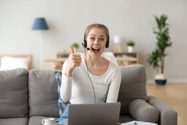 exalterad tjej i headsetet använder laptop visar tummen - video call bildbanksfoton och bilder