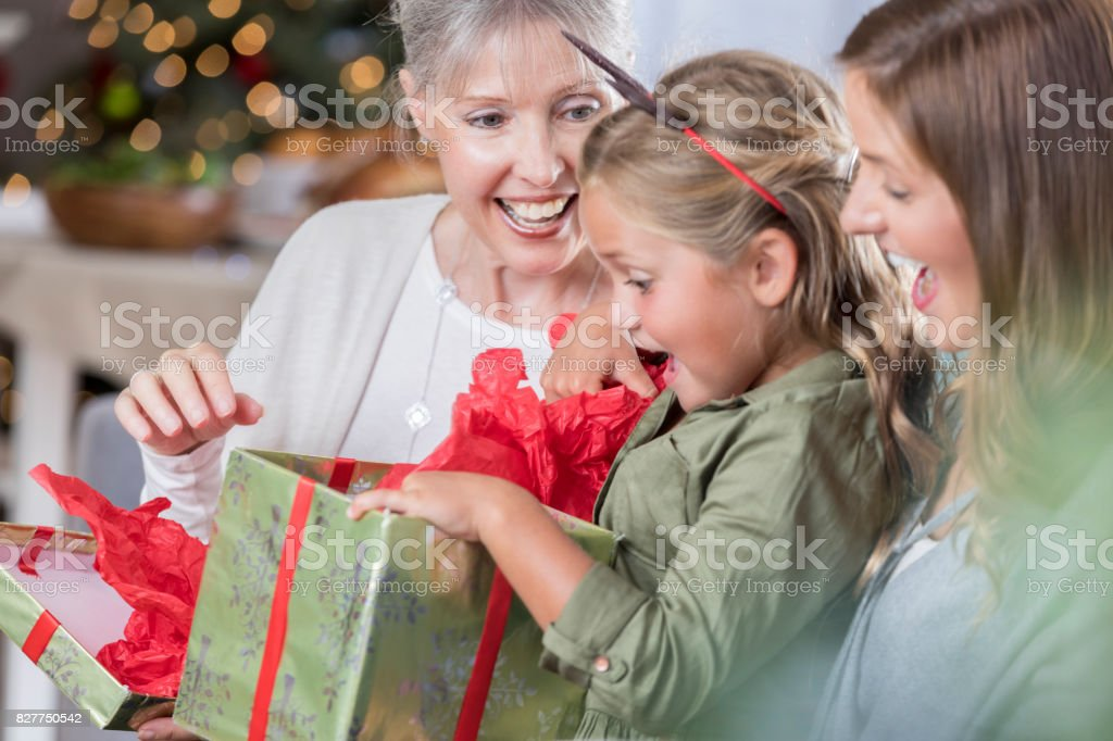 Adorable little girl is delighted while opening up a Christmas...
