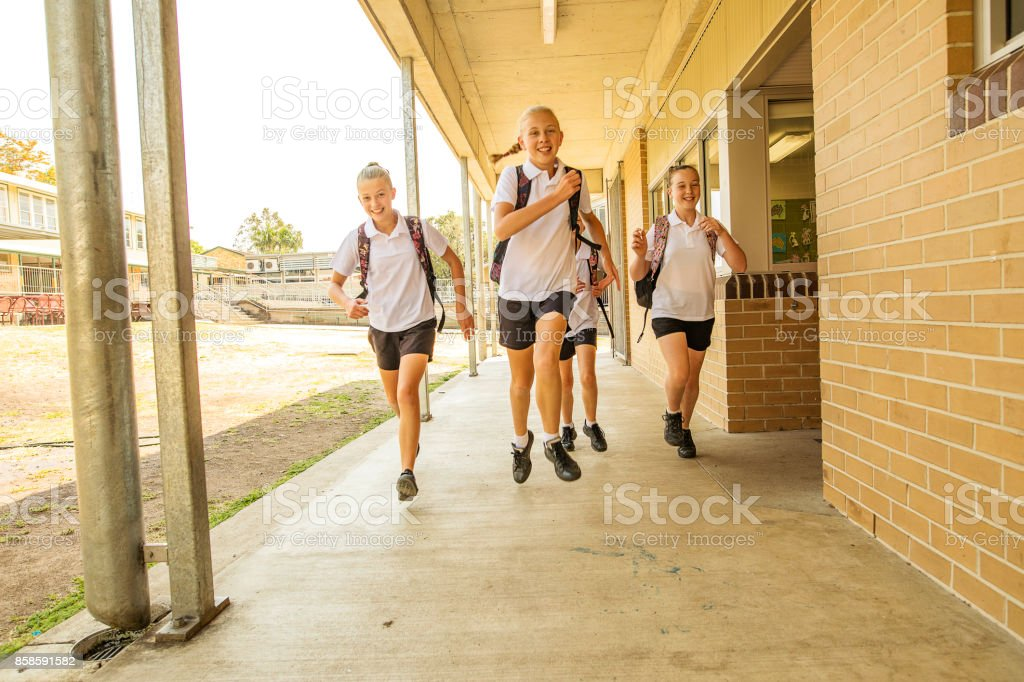 Excited Girl Junior High School Students Running at School stock photo