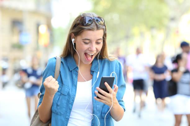 aufgeregt mädchen hören online musik im freien - motivationsmusik stock-fotos und bilder