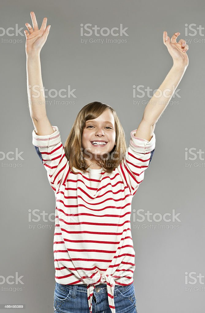 Excited girl Full lenght portrait of cute girl wearing striped blouse and jeans raising her hands and laughing at camera. Studio shot, grey background. 10-11 Years Stock Photo