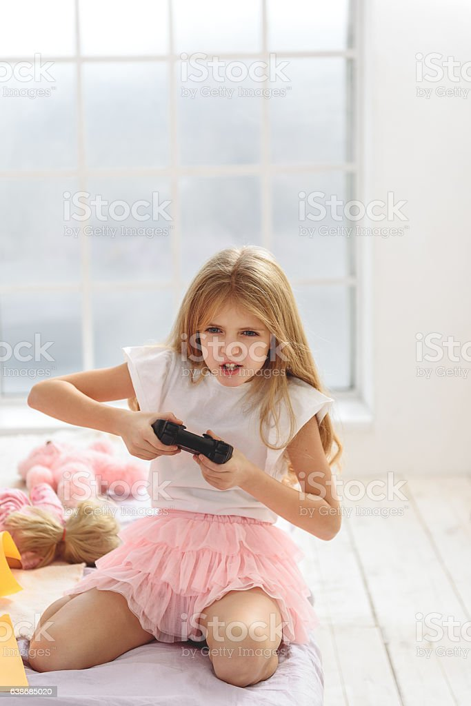 Excited girl playing game console stock photo