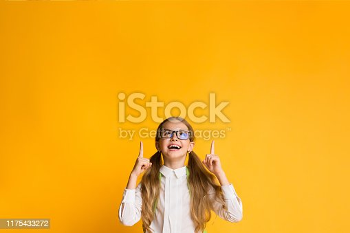 1176772377 istock photo Excited Girl Pointing Fingers Upward Over Yellow Background 1175433272