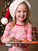 Sweet little girl holds a glass of milk, cookies for Santa and carrots for reindeer on Christmas Eve. She is wearing a Santa hat.