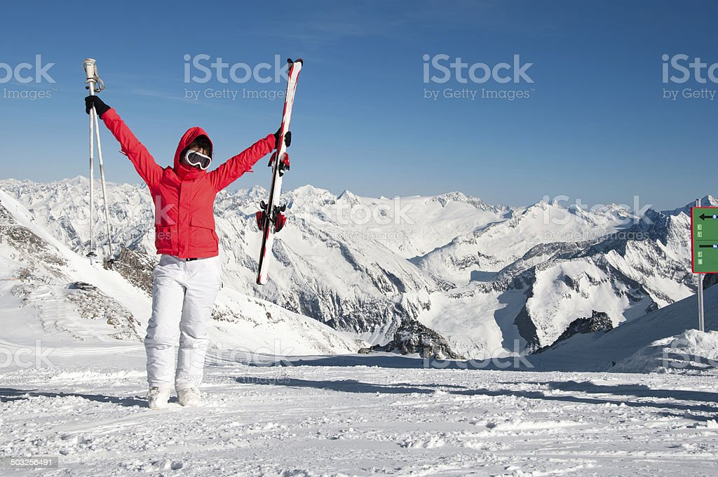 excited Girl standing on top of the mountain with skis stock photo