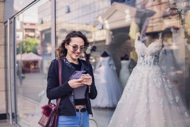 aufgeregtes mädchen mit einem telefon vor einem hochzeitsbekleidungsgeschäft - hochzeitskleider online stock-fotos und bilder