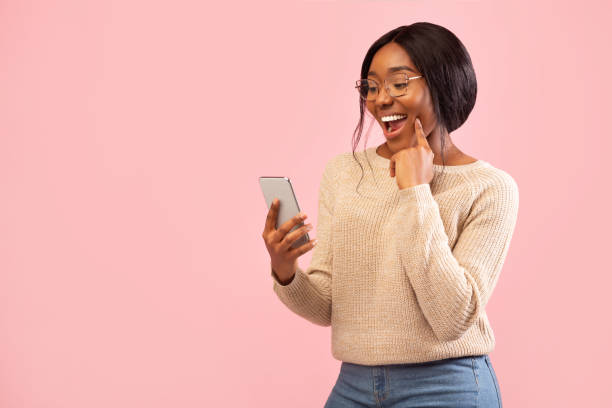 Excited Girl Using Smartphone Holding Finger On Chin, Pink Background Excited African American Girl Using Smartphone Holding Finger On Chin Standing Over Pink Studio Background. Empty Space excitment stock pictures, royalty-free photos & images