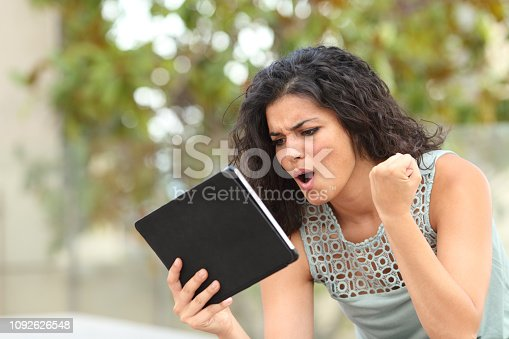 493712130 istock photo Excited girl watching media content on a tablet in a park 1092626548