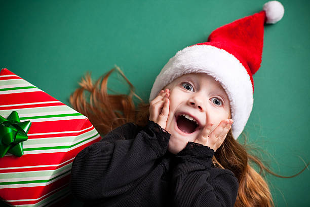 Excited Girl Wearing Santa Hat with Christmas Present stock photo