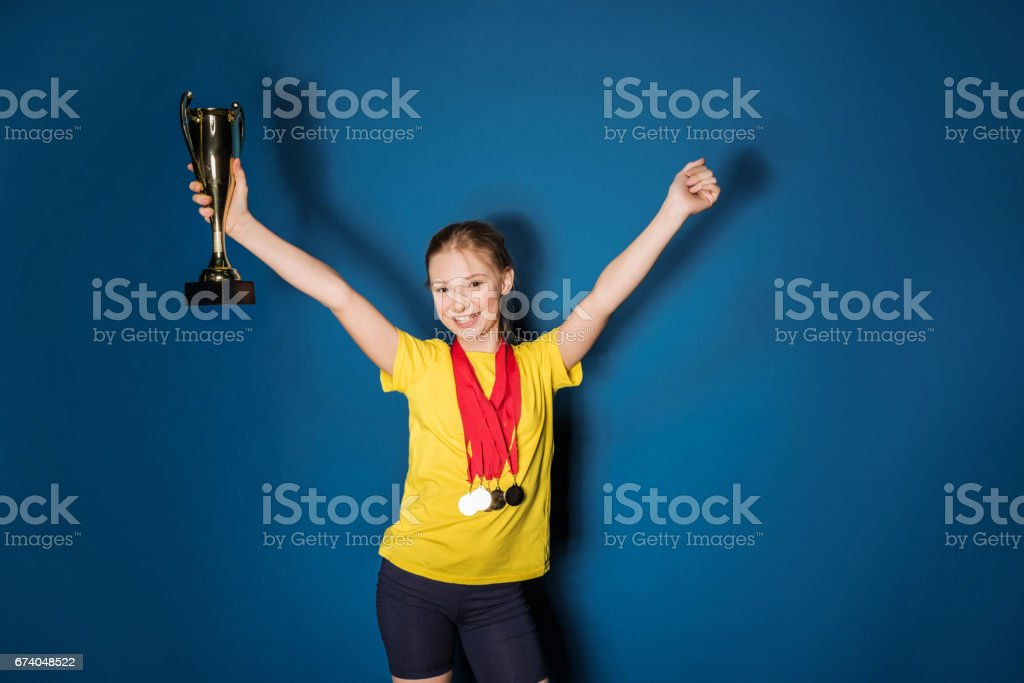 excited girl with medals and trophy cup isolated on blue royalty-free stock photo