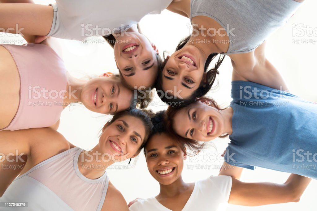 Excited girls hug at training involved in motivational activity Low angle of smiling toned girls stand in circle hugging looking at camera, excited female yogi embrace, feel motivated at yoga session, happy women involved in teambuilding show unity and support Active Lifestyle Stock Photo