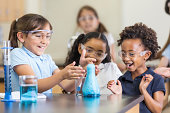 istock Excited girls using chemistry set together in elementary science classroom 498651297