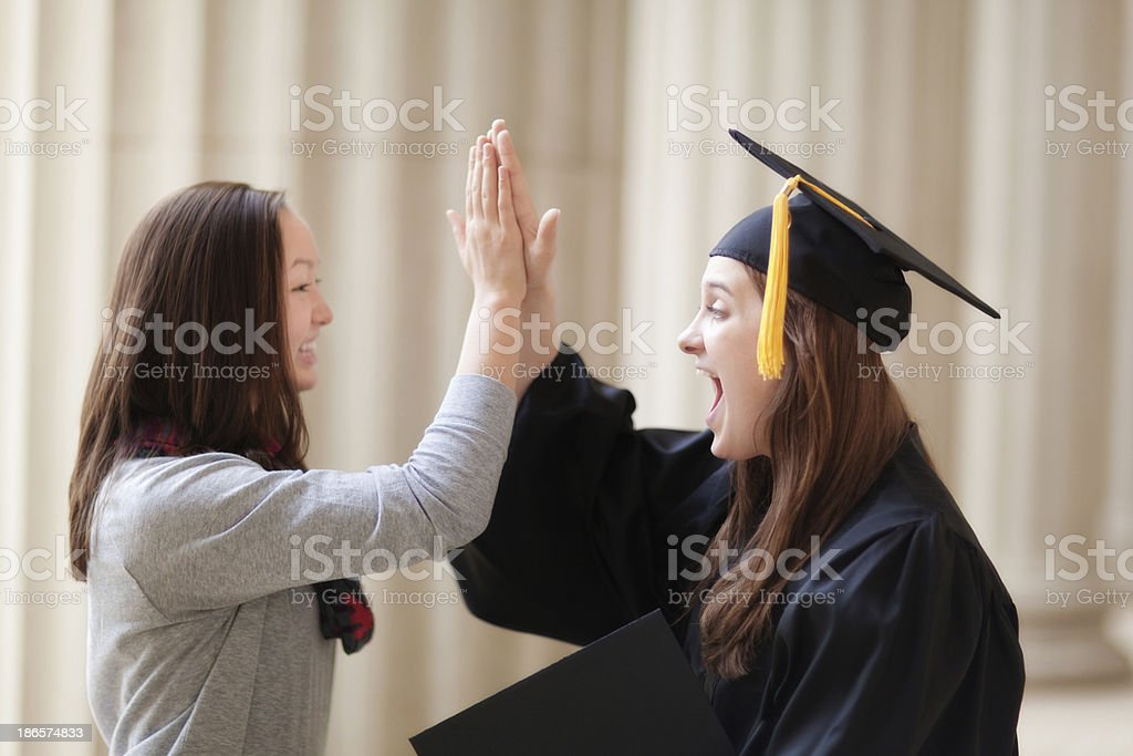 Excited Graduating Woman Student High Five Friends in Graduation Ceremony royalty-free stock photo
