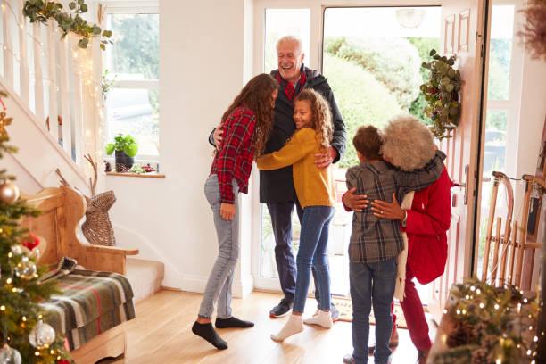 opgewonden kleinkinderen groet grootouders met presenteert bezoeken op kerstdag - christmas family stockfoto's en -beelden
