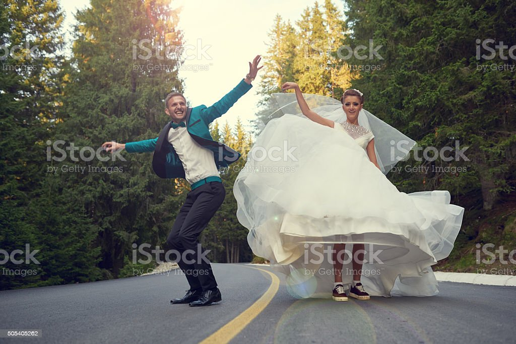 excited grooms jumping on the street stock photo