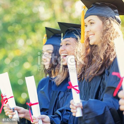 istock Excited group of college girls with their diplomas 614225424