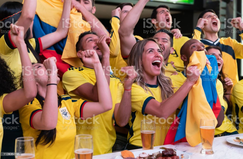 Excited group of Colombian football fans at a sports bar celebrating...
