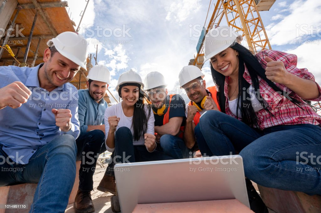 Excited group of construction workers looking very happy watching...