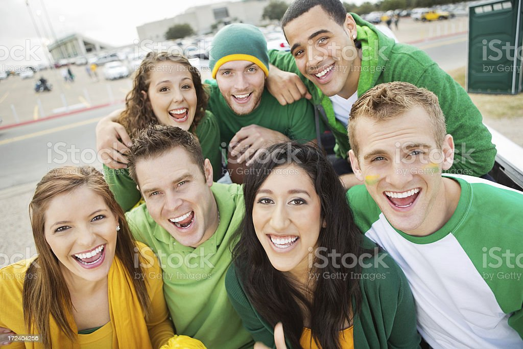 Excited group of football fans cheering on pickup tailgate royalty-free stock photo