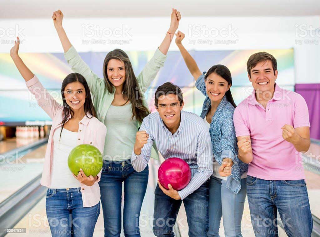 Excited group of friends bowling stock photo