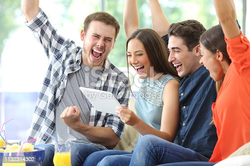 493712130 istock photo Excited group of friends watching media on tablet at home 1132314302