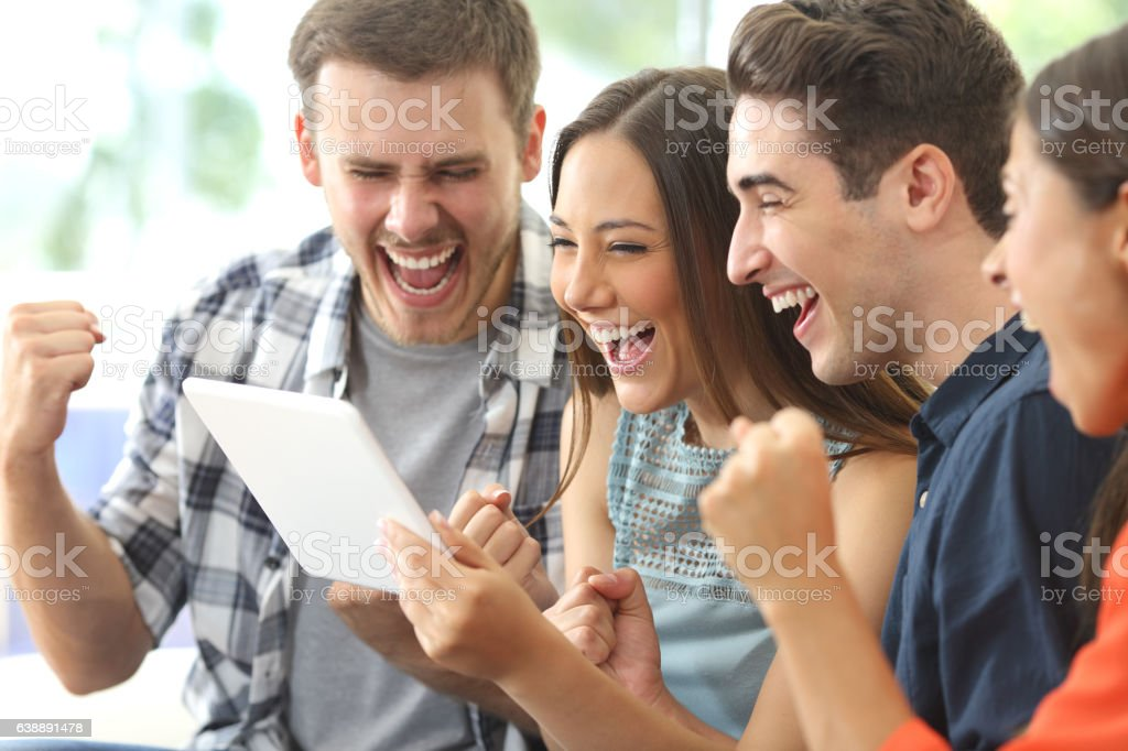 Excited group of friends watching tv from tablet stock photo
