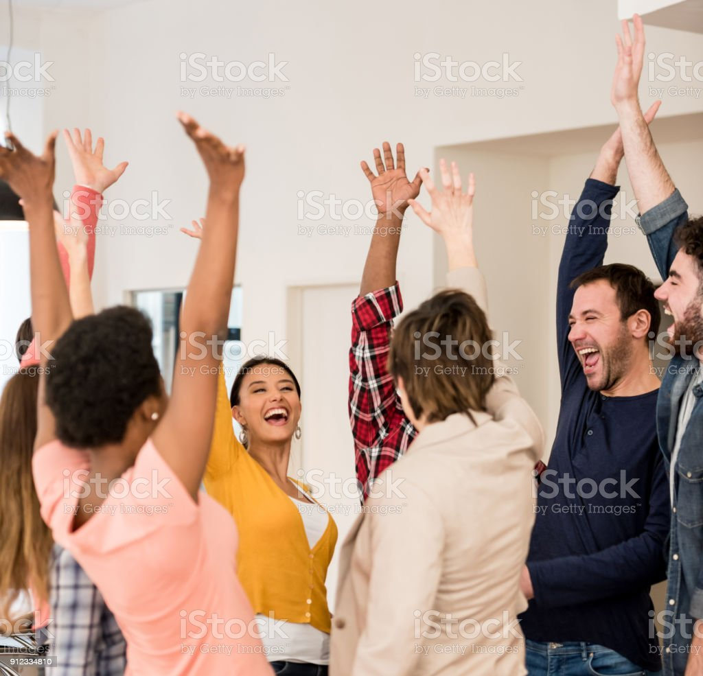 Excited group of people celebrating an achievement at a creative...