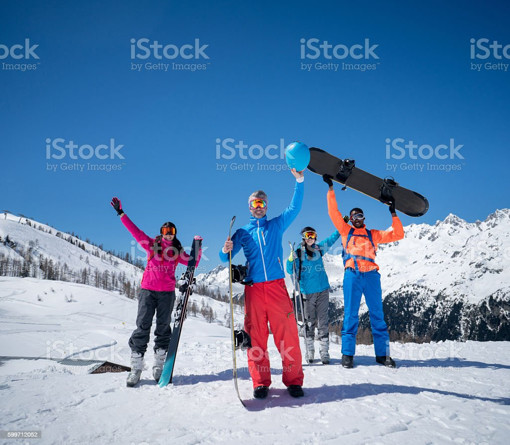 Excited group of people snowboarding looking very happy with arms up...
