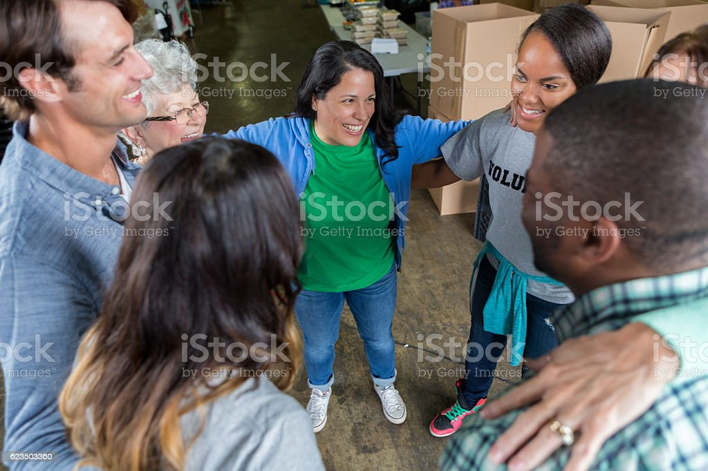 Excited group of people volunteer together during team building exercise stock photo