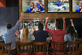 Excited group of people watching the game at a sports bar and celebrating a goal with arms up