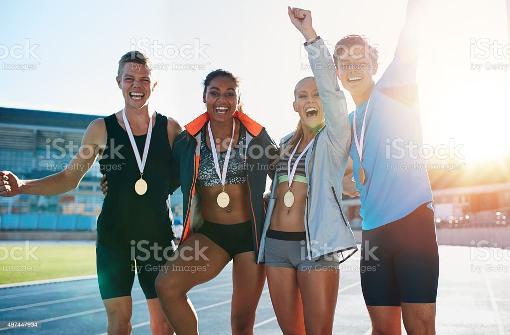 Excited group of runners with medals stock photo