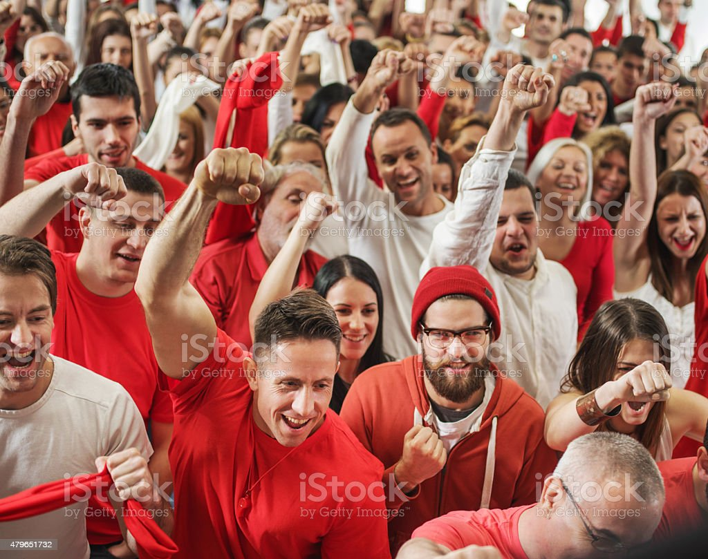Large group of cheerful sport fans shouting and celebrating with...