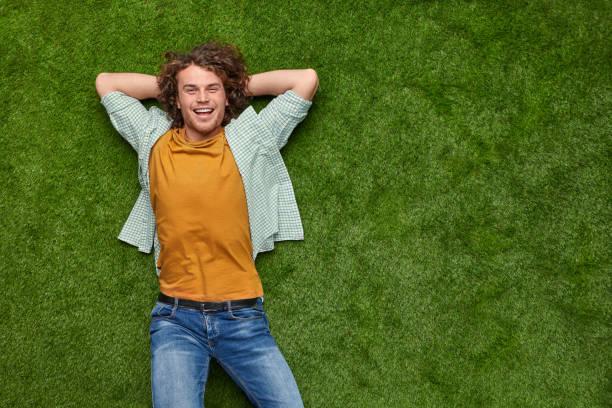 ragazzo eccitato che si rilassa sull'erba - mani dietro la testa foto e immagini stock