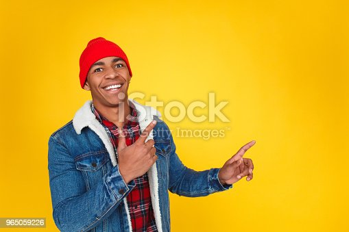 istock Excited guy showing up on yellow 965059226