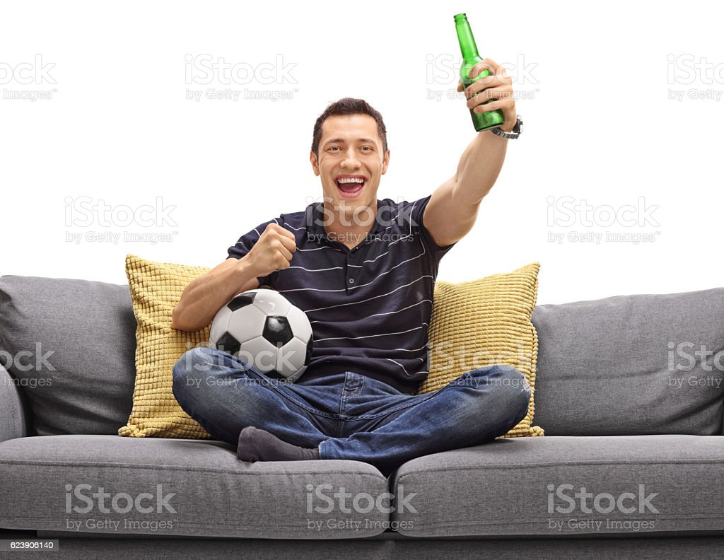Excited guy sitting on couch having beer and watching football stock photo