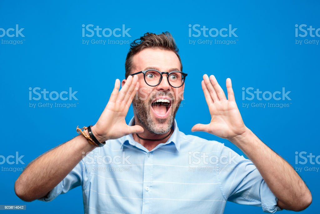 Excited handsome man screaming against blue background Summer portrait of handsome man wearing blue shirt and glasses, screaming. Studio shot, blue background. 30-39 Years Stock Photo