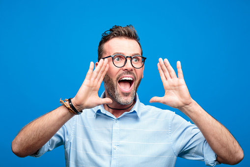 Excited Handsome Man Screaming Against Blue Background Stock Photo - Download Image Now