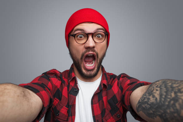 Excited handsome man taking selfie in studio Amazed young unshaven male in glasses and red knitted beanie holding camera and making selfie looking at camera with open mouth over grey studio background mouth open stock pictures, royalty-free photos & images