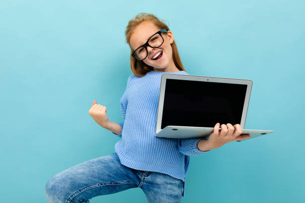 excited happy girl on a blue background holds a laptop, gestures ok stock photo