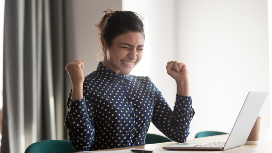 Happy indian woman office worker feeling excitement raising fists celebrates career ladder promotion or reward, businesswoman sitting at desk receive online news, great results successful work concept