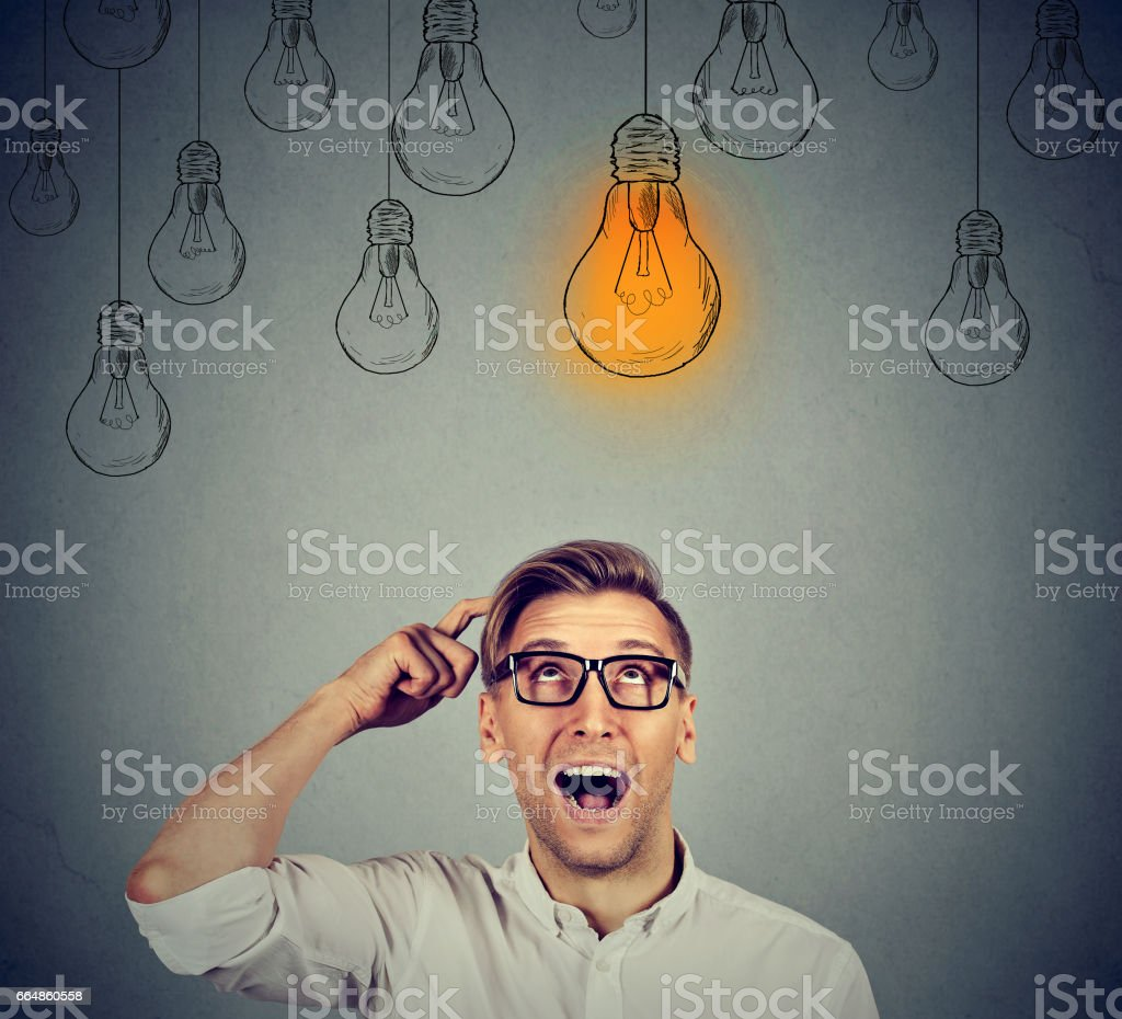 Excited happy man in glasses looking up with light idea bulb – zdjęcie