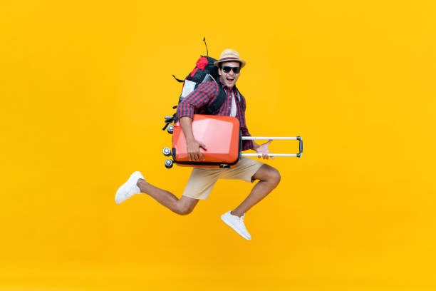 Excited happy young Asian man tourist with luggage jumping stock photo