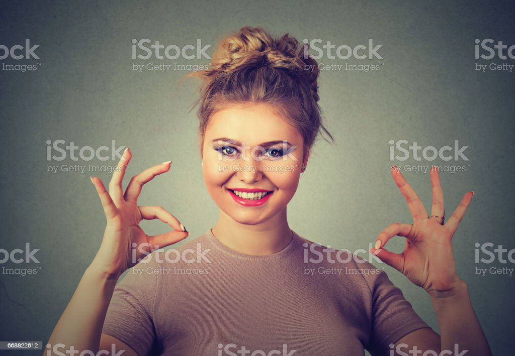 Excited happy young optimistic woman giving ok sign gesture with two hands stock photo