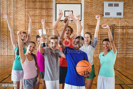 istock Excited high school kids holding trophy in basketball court 676150364
